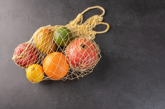Bunch of mixed organic fruit, vegetables and greens in a string bag on dark background.