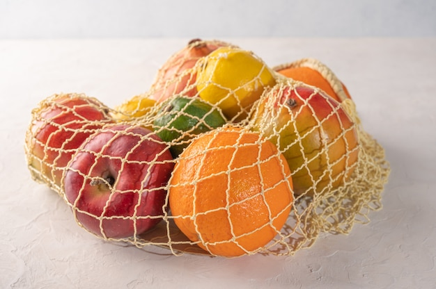 Bunch of mixed organic fruit, vegetables and greens in a string bag on light background.