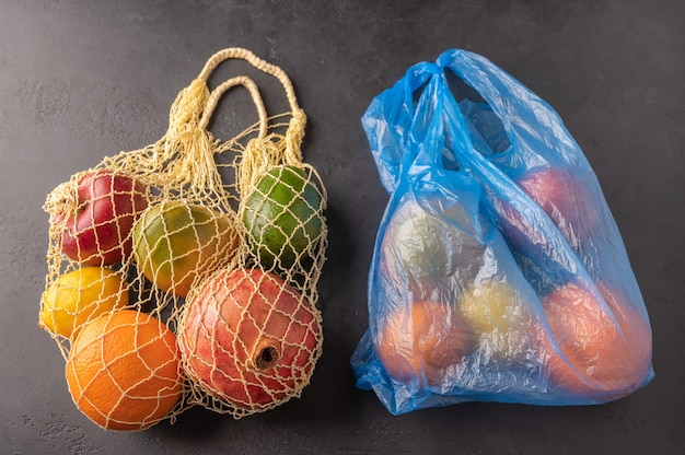Bunch of mixed organic fruit, vegetables and greens in a string bag and plastic on dark background.