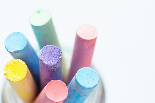 Bunch of multicolored chalks crayons in pencil cup. top view white background.