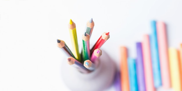Bunch of multicolored pencils in cup chalks. top view white background.