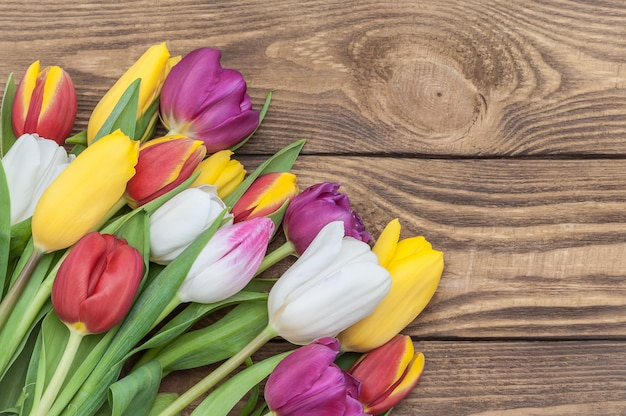 A bunch of multicolored tulips in a corner on a background of light wood.