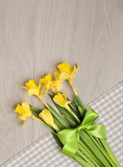Bunch of narcissus flowers on cotton napkin on wood