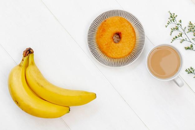 Гроздь бананов и пончик вид сверху