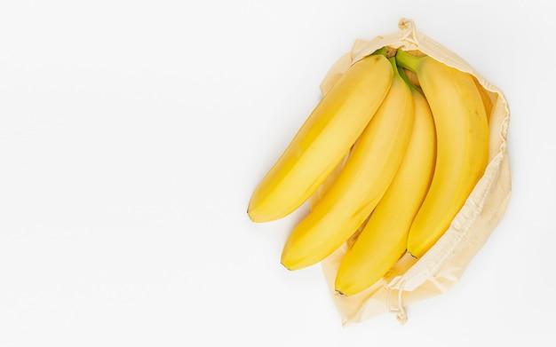 白い背景の上の再利用可能なエコバッグにバナナの束。ゼロウェイスト食品貯蔵。