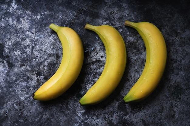 素朴なテーブルの上のバナナの束。フラットレイ。上面図