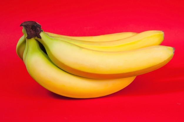 Связка бананов на красном фоне