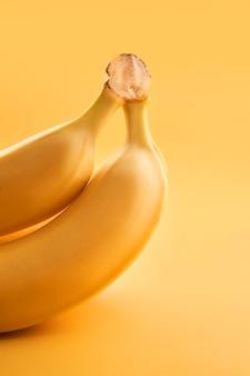 黄色の背景にバナナの束をクローズアップ