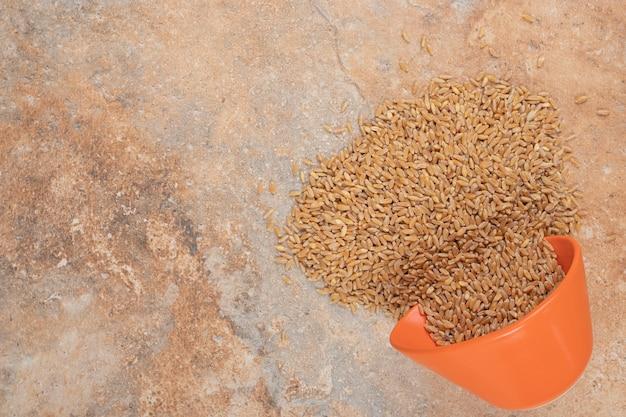 オレンジ色の背景に赤いボウルに大麦の束