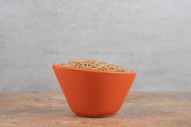 Букет из ячменя в красной миске на оранжевом пространстве.