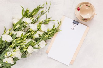 Bunch of beautiful eustoma flowers with clipboard and ceramics empty cup on white background