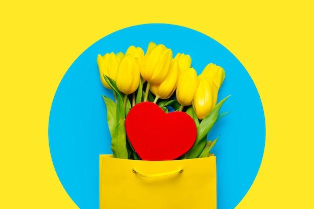 Букет красивых желтых тюльпанов в крутой сумке для покупок и игрушки в форме сердца на чудесном синем фоне
