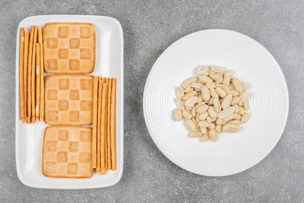 캐슈와 흰 접시에 비스킷과 프레즐의 무리