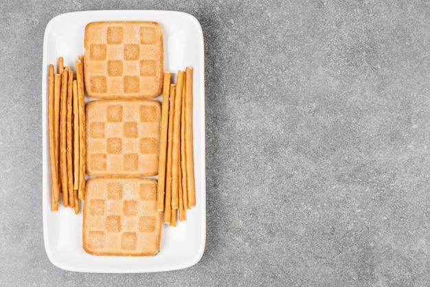 흰색 접시에 비스킷과 프레즐의 무리
