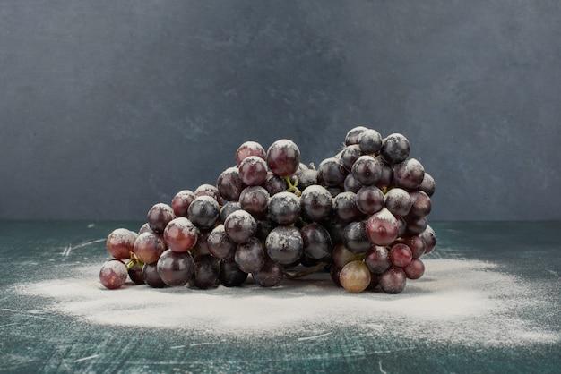 Гроздь черного винограда, украшенная пудрой на мраморном столе.