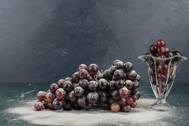 Гроздь черного винограда в стекле и на мраморном столе.