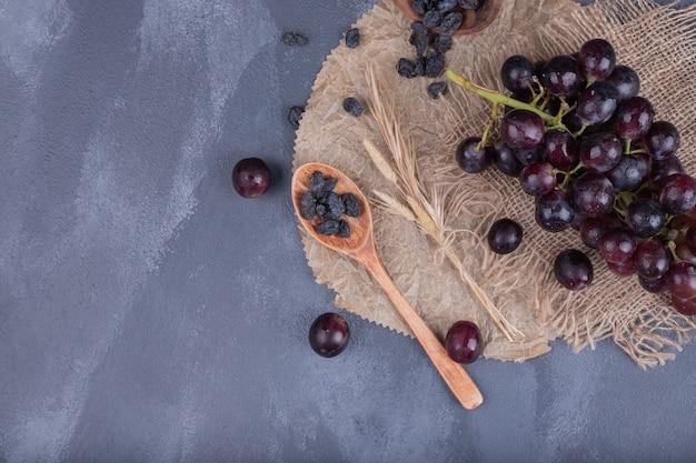 Букет из черного винограда с мешковиной на синей поверхности.