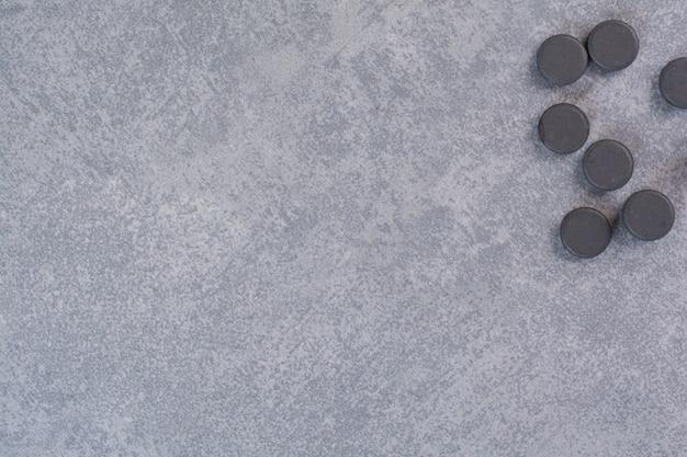 大理石のテーブルの上の黒い丸薬の束。