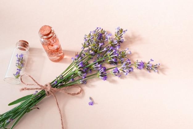꽃이 만발한 라벤더와 필수 라벤더 오일과 꽃이 분홍색 배경에 있는 작은 유리병. 식물성 화장품 개념