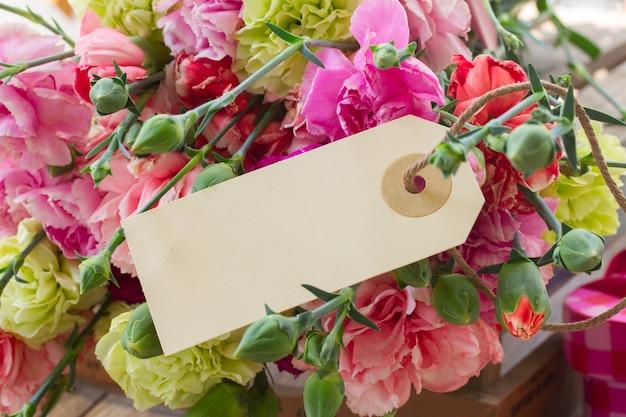 空白のタグが付いたカーネーションの花の束