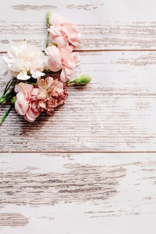 Bunch of carnation flowers with bud on old wooden table