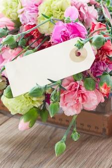 空のタグが付いたカーネーションの花の束
