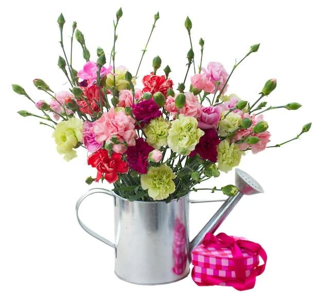 白いスペースで隔離のピンクのギフトボックスとカーネーションの花の束