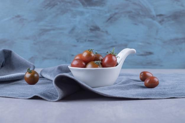 하얀 그릇에 체리 토마토의 무리입니다.