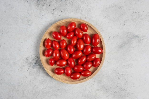 Букет из помидоров черри на деревянной тарелке.