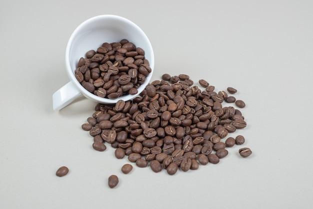 白いマグカップからのコーヒー豆の束
