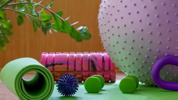 Куча красочных фитнес-аксессуаров оборудование для физических тренировок дома упражнения коврик массажный ролик и шары гантели размытый фон концепция активного здорового образа жизни