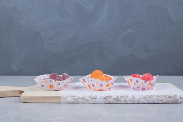 木の板にカラフルなゼリーキャンディーの束。高品質の写真