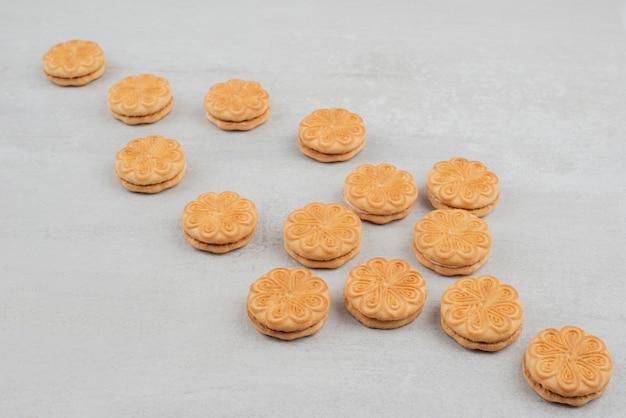 白いテーブルの上のクリームとクッキーの束