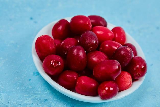 Букет из ягод кизила на белой тарелке. закройте вверх.