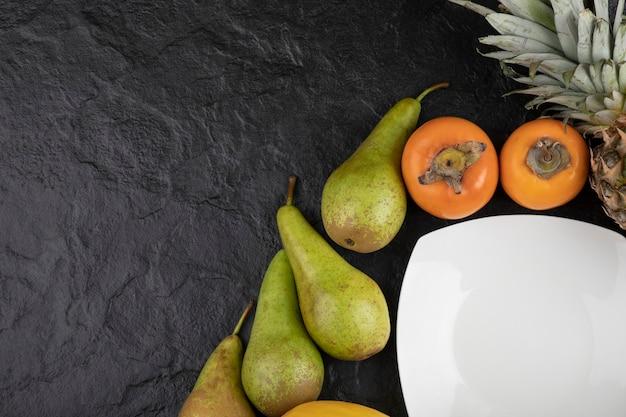 검은 표면에 맛있는 신선한 과일과 빈 접시