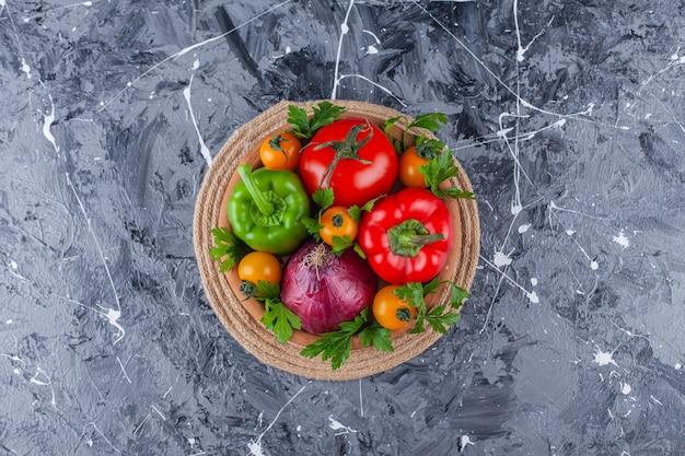 Букет из вкусных здоровых свежих овощей в глиняной миске.