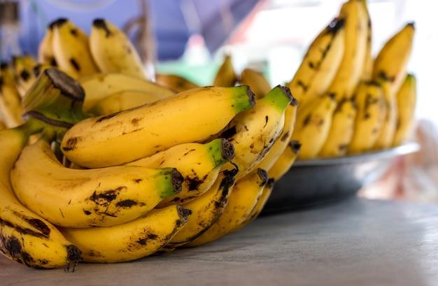 맛있는 익은 노란색 바나나 한 뭉치가 나무 판자 위에 선별적으로 집중되어 있습니다