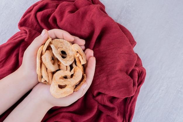 Букет из сушеных яблочных ломтиков в сложенных чашечками руках на белом фоне.