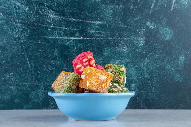 파란색 그릇에 견과류와 말린 과일 펄프의 무리.