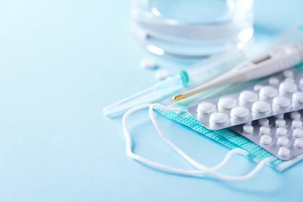 Куча лекарств, лечение простуды. вирусная атака. набор для лечения гриппа - таблетки, капсулы, термометр, защитная хирургическая маска, шприц. копировать пространство баннер. коронавирус ковид-19
