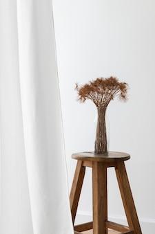 白いカーテンのそばの木の椅子の上のガラスの花瓶に乾いたパピルスの束