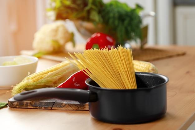 台所のテーブルの調理鍋に乾いたスパゲッティの束