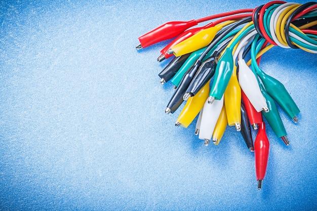 青い背景の電気概念に電気ワニのプラグの束。