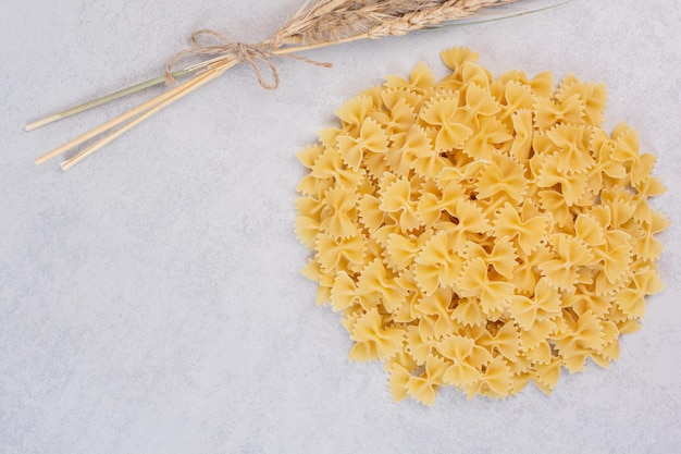Пук макаронных изделий фарфалле на белом столе с пшеницей.