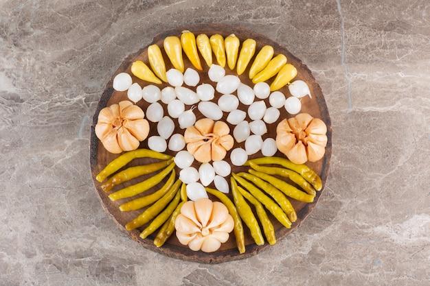 石のテーブルの上に発酵したニンニク、コショウ、玉ねぎの束。