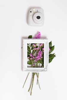 Bunch of flowers and photo frame near camera