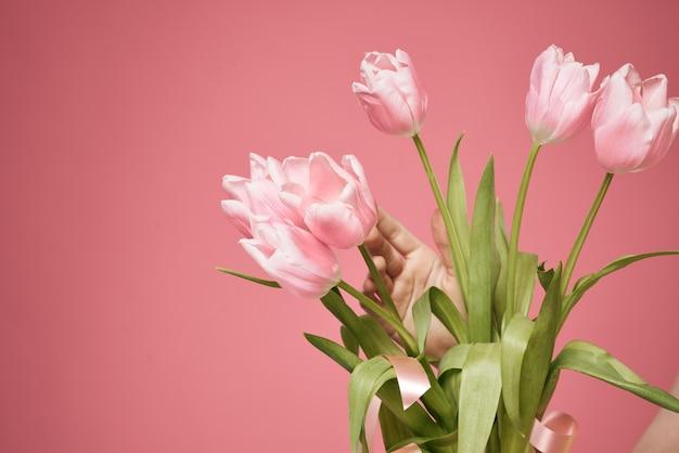 ピンクの壁に贈り物として花の束