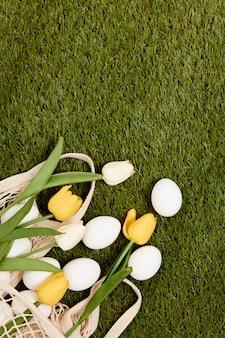 花の束イースターエッグは、緑の芝生の休日の伝統的な装飾の上にあります。 Premium写真