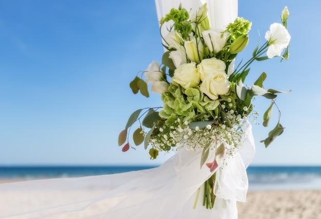 結婚式のための花瓶に花の束。背景には海。