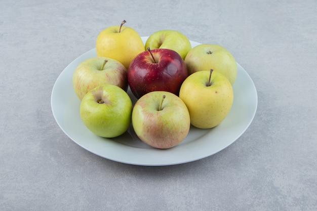 白い皿に新鮮なリンゴの束